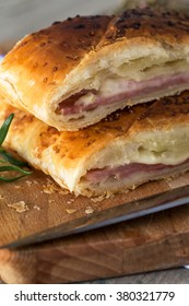Tasty baked bread with ham and cheese on baking paper in close-up.