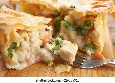 Tasty baked chicken pot pie on wooden board, closeup