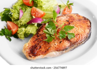 Tasty baked fish on plate close-up