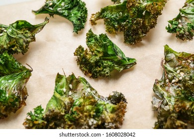 Tasty baked kale chips on light table, closeup