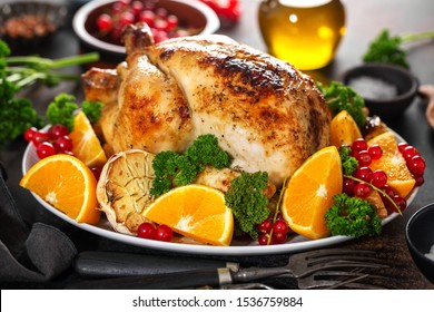 Tasty baked whole chicken with vegetables for Christmas or Thanksgiving Day served on table. Closeup.