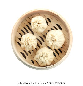 Tasty baozi dumplings in bamboo steamer on white background