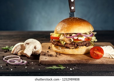 Tasty beaf and mushroom hamburger on dark wooden board pierced with knife, surrounded by french fries, raw meat and black pepper. Free space for text