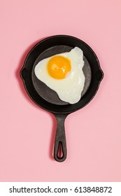 Tasty beautiful food fried egg in pan on fashionable pink background. Minimalistic Concept. Top View.