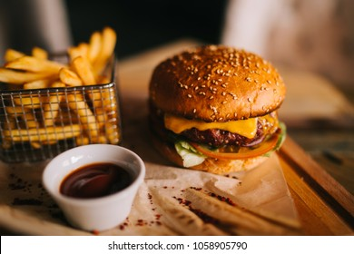 Tasty beef burger with fresh fries. Concept of fast food. Grilled beef burger with lettuce and mayonnaise served on pieces of brown paper on rustic wooden table. An american burger with fried potatoes