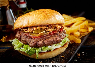 Tasty beef burger with ketchup and ham on a crusty bun served with lettuce, potato chips on a wooden rustic board as a pub lunch