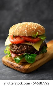 Tasty beef burger with lettuce and cheese on cuttingboard.