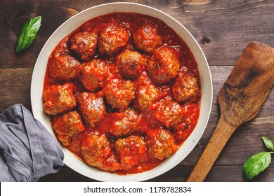 Tasty beef frying meatballs in tomato sauce in a white pan on a kitchen table. Food photography, top view, Sweden traditional cuisine.