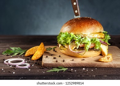 Tasty beef hamburger on dark wooden board pierced with knife, surrounded by french fries, arugula and black pepper. Free space for text?