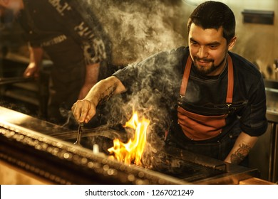 Tasty beef steak cooked on grill with fire and smoke. Beautiful brutal man with bearded face and tattoo cooking meat. Professional chef wearing apron in restaurant kitchen.