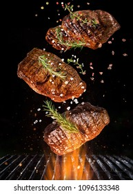 Tasty beef steaks flying above cast iron grate with fire flames. Freeze motion barbecue concept.