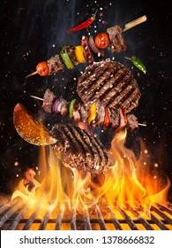 Geschmackvolle Rindsteaks und Spieße, die über Gusseisen fliegen, mit Feuer. Freeze Motion Grillkonzept.