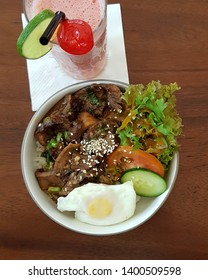 Tasty Beef tounge terriyaki with egg and vegetables salad accompanied with a glass of strawberry juice. Picture was taken in Bandung Indonesia on Christmas 2017.
