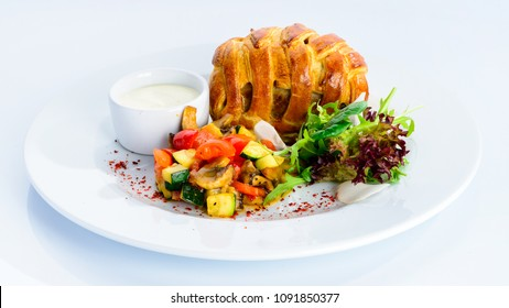 Tasty beef Wellington with pastry crust, appetizing steak dish on the plate on light background