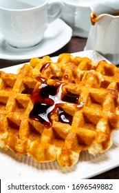 Tasty Belgian dessert, homemade Brussels sugar waffles with dark syrup close up
