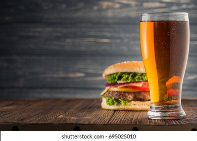 Tasty big burger and beer glass on wood table