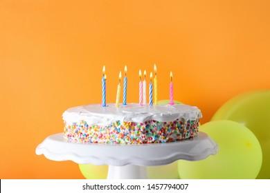 Tasty birthday cake with burning candles and balloons on orange background
