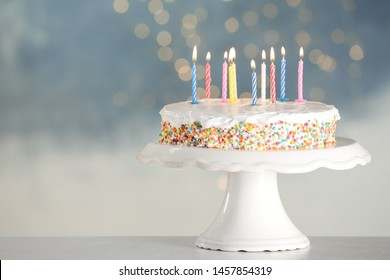 Tasty birthday cake with burning candles on table against blurred lights, space for text