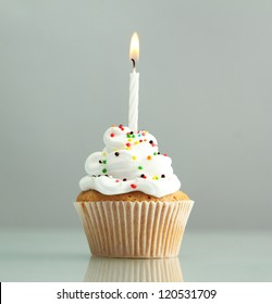 tasty birthday cupcake with candle, on grey background