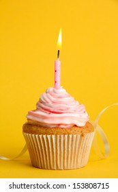 tasty birthday cupcake with candle, on yellow background