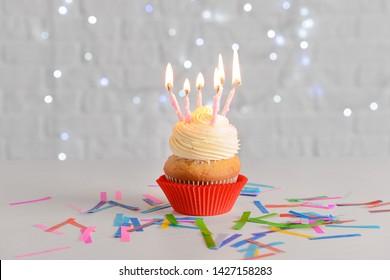 Tasty Birthday cupcake on white table