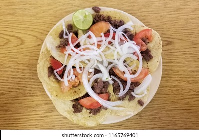 Tasty bistec taco with steak, onion, tomato, red sauce, avocado and lemon over traditional Mexican tortilla bread
