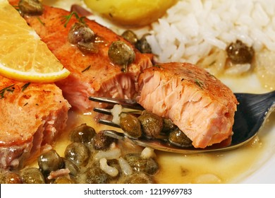 Tasty bite of salmon piccata with creamy lemon caper butter sauce on fork with rice, closeup.