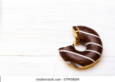 Tasty bitten donuts with icing and chocolate on white wooden background, copy space