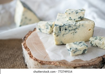 Tasty blue cheese on a wooden background and burlap. Dorblu cheese pieces
