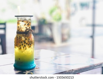 Tasty blue-ocean Italian soda drink closeup on a table background with view from high angle. Bottle glass of blue soda and yellow passion fruit with ice & straw decoration