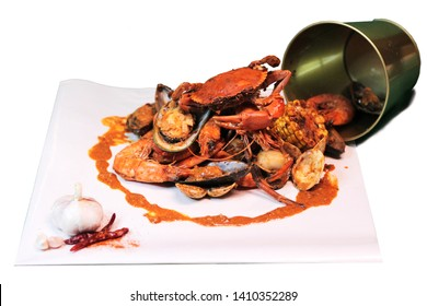 Tasty Boiling Seafood in the bucket with crab shrimp prawn mussel clam corn on the cob and sauce on white background