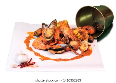 Tasty Boiling Seafood in the bucket with  shrimp prawn mussel clam corn on the cob and sauce on white background