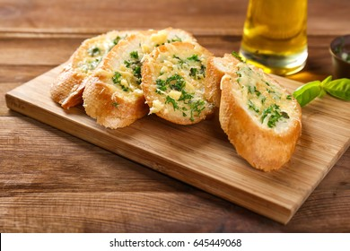 Tasty bread with garlic, cheese and herbs on kitchen table