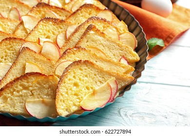 Tasty bread pudding with apple in baking dish on table