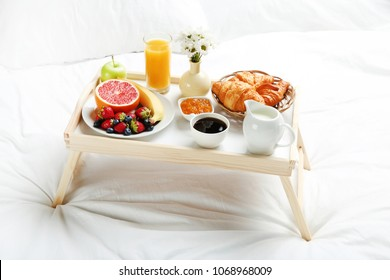 Tasty breakfast in bed on wooden tray