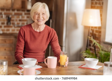 Tasty breakfast. Cheerful senior woman sitting at the kitchen table, having breakfast and posing for the camera, smiling broadly