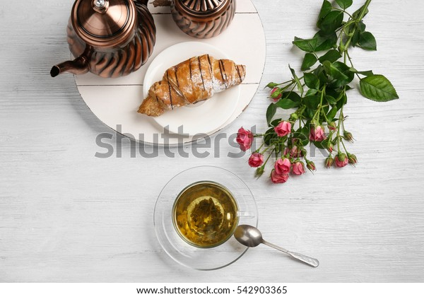 Tasty breakfast with cup of tea and fresh croissant on white table