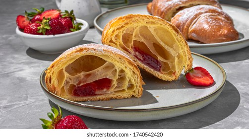 Tasty breakfast. Fresh croissants and strawberries with a pouring sugar powder  black coffee and a milk jug. Horizontal banner