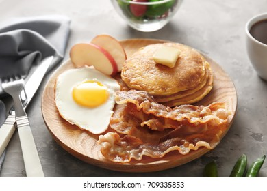 Tasty breakfast with fried egg, pancakes and bacon on wooden board