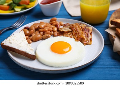 Tasty breakfast with fried egg, sandwich and bacon served on blue wooden table, closeup