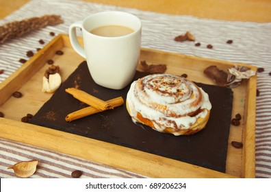 Tasty breakfast with homemade cinnamon roll and fresh coffee. Food background.