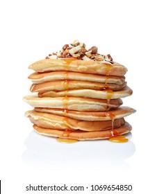 Tasty breakfast. Homemade pancakes with crushed hazelnut, honey or maple syrup isolated on white background