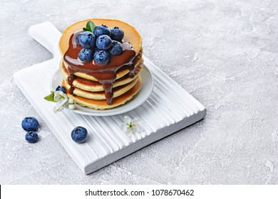 Tasty breakfast. Homemade pancakes with fresh blueberry and melted chocolate on white wooden cutting board on gray concrete background
