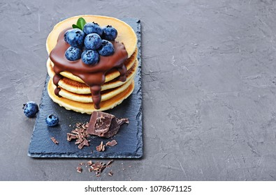 Tasty breakfast. Homemade pancakes with fresh blueberry and melted chocolate on black slate board on gray concrete background