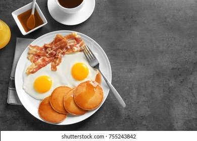 Tasty breakfast with pancakes, fried eggs and bacon on grey background