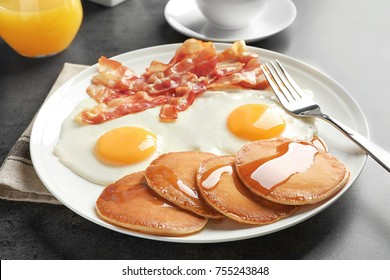 Tasty breakfast with pancakes, fried eggs and bacon on table
