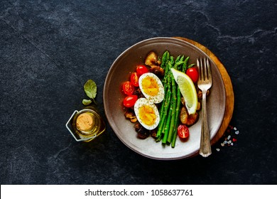 Tasty breakfast plate flat lay. Aspargus, tomatoes, mushrooms and eggs over black stone copy space background. Energy boosting food concept. Top view.