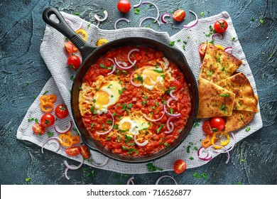 Tasty Breakfast Shakshuka in a Iron Pan. Fried eggs with tomatoes, red, yellow peppers, onion, parsley, Pita bread and herbs. Healthy Food