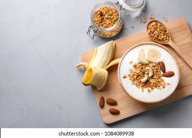 Tasty breakfast with yogurt, banana and granola on table, top view