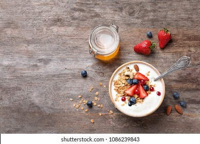 Tasty breakfast with yogurt, berries and granola on wooden table, top view